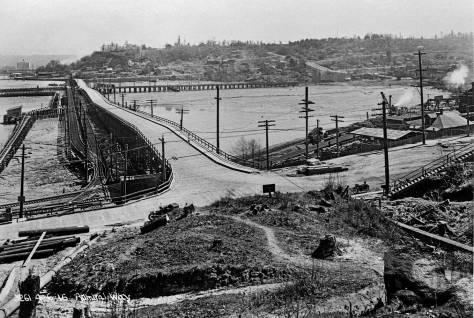 THEN: In 1852 many of Seattle's first pioneers removed from Alki Point by dugout canoe for the deeper and safer harbor along the east shore of Elliott Bay (our central waterfront). About a half-century later any hope or expectation that the few survivors among these pioneers could readily visit Alki Beach and Point by land were fulfilled with the timber quays and bridges along Spokane Street. (Courtesy Seattle Municipal Archive)