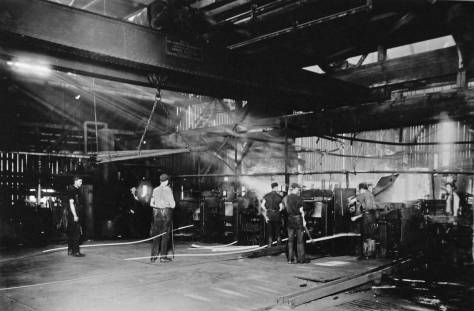 This dark interior of the early plant's 12-inch rolling mill dates from about 1910.  We can imagine the mix of warm light from the furnaces with the cool blue light falling from the mill's high windows.