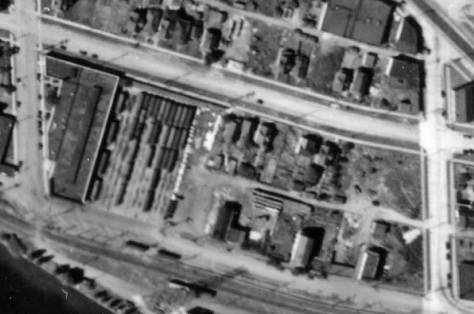 A detail from the 1936 aerial coverage of Seattle.  The trolley barn is far left at the corner of Phinney Ave. N. and N. 34th Street (at the bottom of the detail) with Evanston Ave. N., far right.  The house with its northwest corner showing in the feature photograph, is mid-block on the south side of N. 35th Street between Evanston and Phinney.  Between it and the rows of parked trollies the scattering of white forms - the same as those at the top - appear.  (Courtesy, Ron Edge)