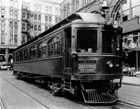 The Seattle-Tacoma Interurban's plush parlor car waiting on Occidental Ave. with the Seattle Hotel behind it and the Inteurban Building on the right.  (Courtesy, Lawton Gowey)