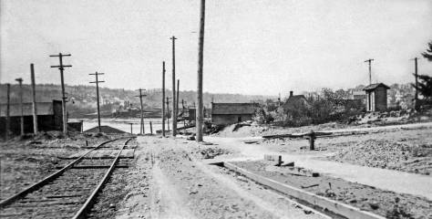THEN: Looking west down Ewing Street (North 34th) in 1907 with the nearly new trolley tracks on the left and a drainage ditch on the right to protect both the tracks and the still barely graded street from flooding.  (Courtesy, Michael Maslan)
