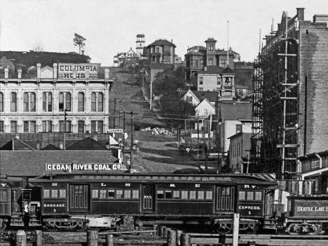 THEN: In this 1887 look up Columbia Street from the waterfront is the bell tower of the fire station, tucked into the hill on the right. It would soon fail to halt the city's Great Fire of June 6, 1889. The station and everything between it and Elliott Bay were reduced to ashes, smoldering bricks and offshore pilings shortened like cigars. (courtesy, Kurt Jackson)