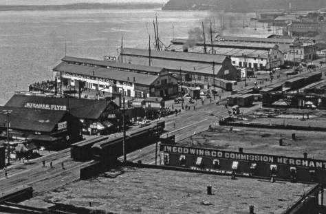 Railroad Ave. ca. 1903 showing the then new long finger piers north of Madison Street.  The shorter piers to the south (left) of Madison were built after the Great Fire of 1889.  They would be either moved further into the bay on new pilings are replace with longer piers like the Grand Trunk Dock and Colman Dock.