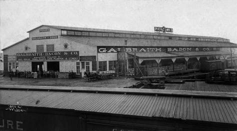 An early record of Pier 3 (54 since 1944) and its first tenant Galbraith and Bacon.  The photo was taken in 1900, some little while before the photographer, Aders Wilse, return to Norway and the call of his wife who left Seattle first for a visit back to the homeland and then decided to not return here.   Wilse then obeyed she who must be.  Soon he became a Norwegian national treasure, and the photographer to its King and Queen and all their little princes and princesses.
