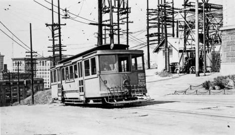Near it last day, a Yesler Way Cable Car approaches Seventh Avenue on Yesler Way, now the eastern border of the 1-5 Freeway.  The photograph was taken by a trolley and cable enthusiast in 1940.  (Courtesy, Lawton Gowey)