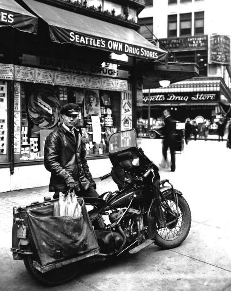 THEN: A motorcycle courier for Bartell Drugs poses before the chain's Store No. 14, located in the Seaboard Building at the northwest corner of Fourth Avenue and Pike Street, circa 1929.  (Courtesy Bartell Drugs)