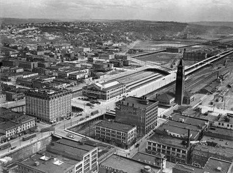 Both the Great Northern (with the tower) and Union Pacific Depots, are found on the far side of Jackson Street in this ca. 1913 look down from the new Smith Tower.  A second tower, appearing on the bottom-right, is part of Firehouse No. 10 at the northwest corner of Main Street and Third Ave. South.  There is, of course, as yet no Second Ave. Extension.  (Courtesy, Lawton Gowey)
