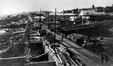 1889 ruins along Front Street looking north from near the foot of Cherry Street.  The central tower of the Stetson-Post terraced apartments appear on the top-right corner.