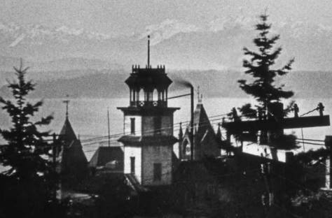 The Coppins Water Tower seen from the tower of the Haller Mansion at the northeast corner of James Street and Terry Avenue.   The towering Central School at Sixth and Madison and the Olympic Mountains, across Puget Sound appear beyond the water tower.