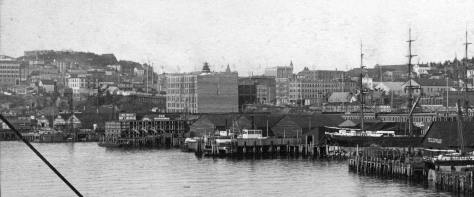 The central waterfront in 1890 photographed from the King Street coal dock.  The Gilmore Block is at the center of the scene with its corner tower still under construction.  The foundation for the Denny Hotel marks the horizon on Denny Hill.