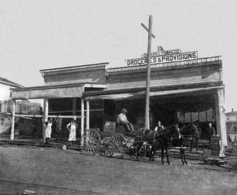 THEN: Charles Louch's grocery on First Avenue, north of Union Street, opened in the mid-1880s and soon prospered. It is possible – perhaps probable – that one of the six characters posing here is Louch – more likely one of the two suited ones on the right than the aproned workers on the left. (Courtesy RON EDGE)