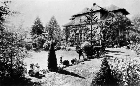 A wider view of Totem Place.  Although blasted by back light both Daddy Standley, near the center, and his tall sculpture made of shells, far right, are apparent.  (Courtesy John Cooper)