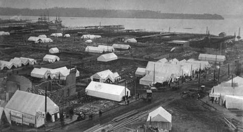 """The Post-Fire ruins and tents, this time from the Katzenjammer tower.  Mill Street (Yesler Way) crosses to the right from the lower-left corner.  Jefferson Street meets it from the lower-right corner. West Seattle is on the horizon. """"Our corner"""" of Main and Second (Occidental) is upper left, below the tall ships."""