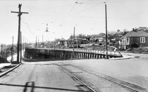 THEN: From 1909 to the mid-late 1920s, the precipitous grade separation between the upper and lower parts of NE 40th Street west of 7th Ave. NE was faced with a timber wall. When the wall was removed, the higher part of NE 40th was shunted north, cutting into the lawns of the homes beside it. (Courtesy, Lawton Gowey)