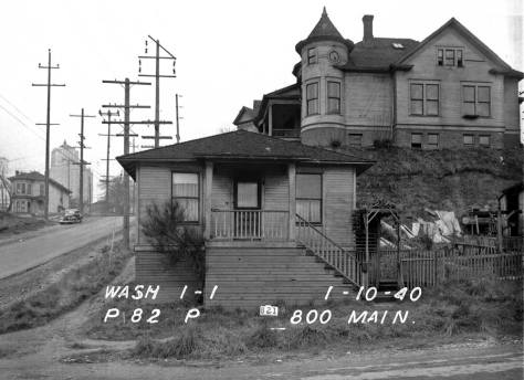 The towered manse holding to the east side of 8th Avenue, one lot north of the corner and the much smaller box with the 800 Main address written on the negative. Note Harborview Hospital up the way. Again, this big home appears clearly on the far left of the featured photo at the top. (Courtesy, Lawton Gowey)