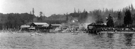A steady but searching eye might find some of the same Schmitz treeline standing about thirty years earlier in this ca. 1912 look east over the at play Alki Beach to the West Seattle ridge.