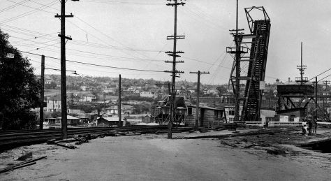 "Another distant glimpse of the ""Wallingford Wall"" on N.E. 40th Street, this time looking through Eastlake from the south end of both the Latona Bridge with the lifted spans, and the new University District Bridge, a work-in-progress out of frame to the right. (Courtesy, Seattle Municipal Archive.)"