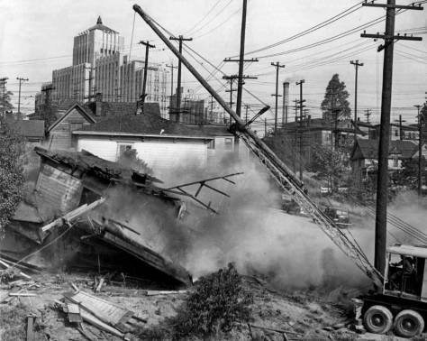 "The caption for this Seattle Times snapshot from Oct. 7, 1940 reads, ""Cr-r-r-a-a-ac-ck! Smash! And down went an old frame home at Seventh Avenue and Washington Street as wreckers razed the first of 143 old bildings to be demolished to make room for the Seattle Housing Authority project on Yesler Hill, where modern buildings will replace t he dwelling which have grown shoddy and bleak since the days many years ago, when they housed Seattle pioneer families."""