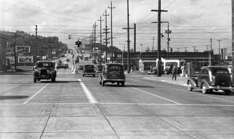 Looking north on Aurora ca. 1933 thru its stop-lighted intersections with Broad and Mercer, together the busiest crossroads in Seattle and most dangerous. Both Broad and Mercer were tunneled under Aurora in the 1950s.