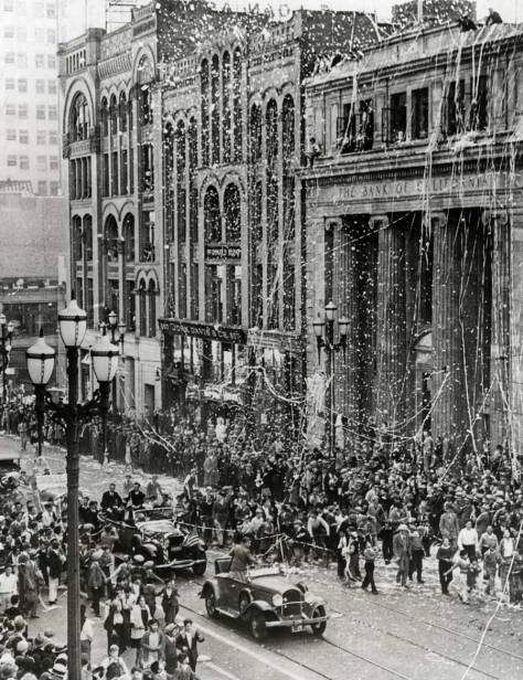 A parade on Oct. 8, 1931 for the trans-Pacific pilot Clyde Pangborn. The Ionic column clad Bank of Ca;lifornia is on the right. The Haller Building, far left, and inbetween them the McDonald Building. (Gratitude, Ron Edge)