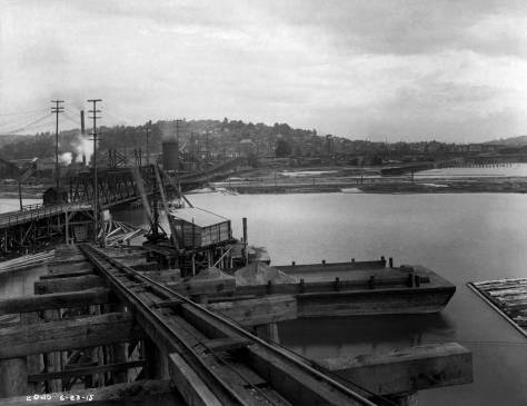 THEN: James Lee, for many years an official photographer for Seattle's public works department, looks south over Ballard's Salmon Bay a century ago. Queen Anne Hill marks the horizon, with a glimpse of Magnolia on the far right. (Courtesy, Museum of History and Industry)