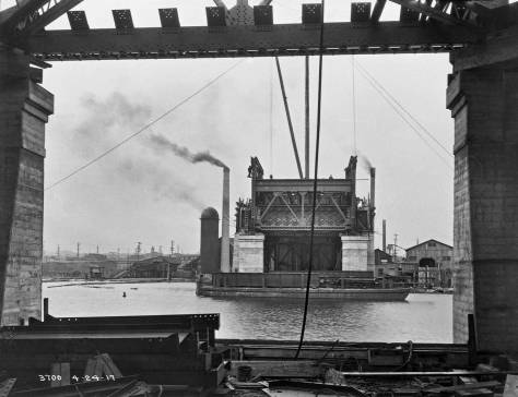 Dated April 24, 1917, the piers, north and south, are up, but not the teeter-totter wings for the bascule, and the bridge would consequently not be ready for the Lake Washington Ship Canal's July 4, 1917 inaugural opening. Again - as noted in the caption above this one - note that the burning tower and chimney on the left and the metal warehouse on the right, both appear in the earlier photo above this one. This photo then was our primary clue for locating the photo above it.