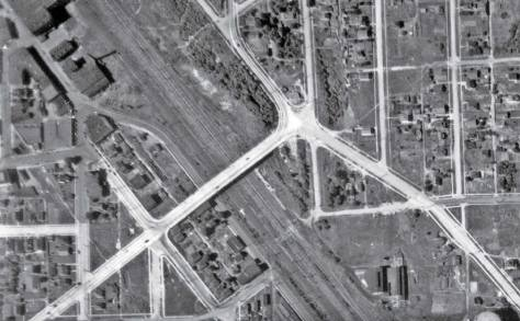 """This 1936 aerial for mapping centers on the nearly new Albro Place bridge that crossed above the wide swath of railroad tracks and replaced the ground level plank-paved crossing on Graham Street. The remnants of this last can be detected as a lighter-shade of covering a little less than a block south (right) of the overpass. The disturbed ground cover on Juneau Street, which support the pedestrian overpass into Georgetown can also be """"sensed"""" to the north (left) of the Albro Bridge, about one long block distant. Half of the Seattle Electric Company's gas tank is revealed at the photo' s bottom-right corner. Part of the brewery shows at the upper-left corner. (Courtesy: Museum of History and Industry)"""