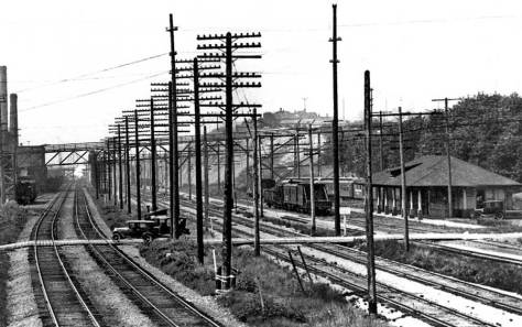 "Historian Kurt Armbruster helped in our sizing of the Georgetown RR Depot with this look at from the west side of the mainline tracks. Some of the towering east facade of the Rainier Brewery crowds the left border. The planks crossing the tracks to this side of the depot served as the first near-at-hand vehicular access between Georgetown and Beacon Hill. The pedestrian viaduct in line with Juneau Street, which figured in a feature hear and can also be found in the ""Edge Links"" below, also shows here. (Courtesy Kurt Armbruster)"