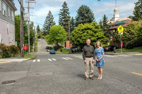 """NOW: Descendants Stuart and Michele Kenney pose at the same intersection, sans trestle. The former Ashton Grocery building, shown in the """"then"""" view, remains, at left."""