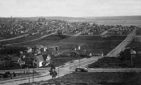 THEN: We imagine that the photographer A.J. McDonald waited for one of his subjects, the cable car to Queen Anne Hill, to reach the intersection of Second Ave. N. and Aloha Street below him before snapping this panorama in the mid-1890s.