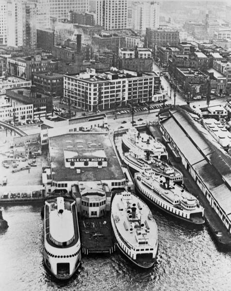 The deco Colman Dock post-WW2 with a Welcome Home sign on the roof and Black Ball's flagship the Kalakala on the right.