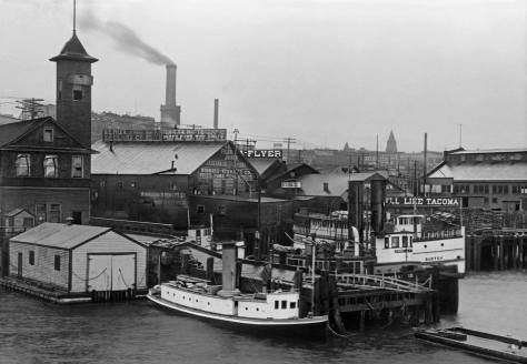 "THEN: This post-1889 waterfront block of sheds and ships was replaced in 1911 by the Grand Trunk Pacific Dock, described at the time as ""the largest wooden finger pier in North America."" The exception was Fire Station No. 5 on the left at the foot of Madison Street. A brick station replaced it in 1913. (Museum of History & Industry)"