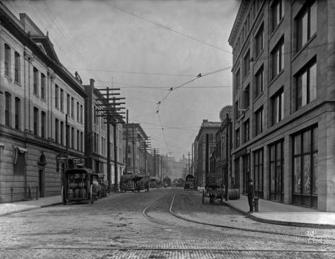 THEN: This view looking east from First Avenue South on Jackson Street in 1904, is still four years short of the Jackson Street Regrade during which the distant horizon line near 9th Avenue was lowered by more than 70 feet. (Courtesy Museum of History and Industry)