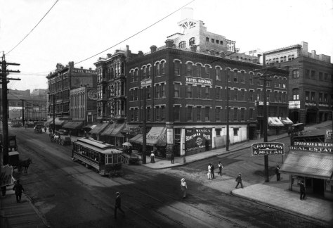 THEN: An electric trolley heading north for Green Lake completes its crossing of Seneca Street, continuing its passage beside a diverse cluster of one small tailor shop – at the center – and four hotels named right-to-left, the Hotel Ramona, the Yates, the Yellowstone, and at the corner with University Street, the Hotel Diller. (Courtesy, MUSEUM of HISTORY & INDUSTRY)