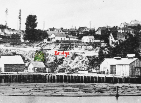 """The bridge over the Seneca Street ravine is marked in this detail from the Peterson & Bros. 1878 panorama of the nearly new Front Street Regrade (1876). The green coloring clumsily """"enhances"""" the green growth that is attached to the log-constructed retaining wall on the west side of Front Street. The vegetation was encourage or fed by the drainage on Seneca."""