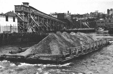 A topped-off barge heading into the bay from the terminus for the Denny Regrade's main conveyor Belt.