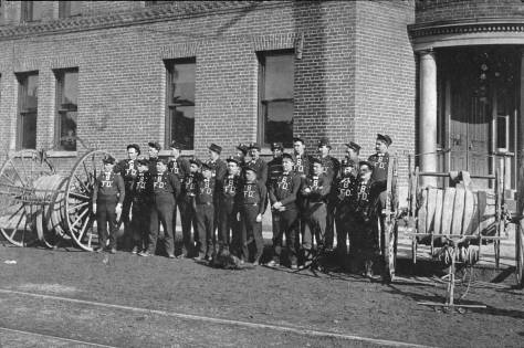 Before building its own quarters Ballard's Burke Avenue, the Shingle Capitol's fire department was lodged in its brick City Hall. Here volunteers (mostly) pose with two of the department's hose reals. On August 25, 1902 the Ballard hose team won an invitational race and $124 on Firemen's Day. Running on Union Streeet between fourth and Seventh Avenues they made a run of 300 yards, laid a line (of hose), and had water running in forty-one seconds. The Columbia Cityi team was second in forty-nine seconds. At two extremes, the Seattle Team did not run, and the Hoquiam team ran too well. It easily made the best run, but went oo far, passing the first fire plug entirely. Hence no record of their run could be taken.