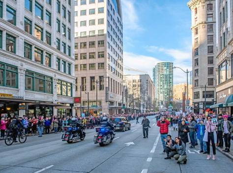 """NOW: For his repeat Jean Sherrard, of course, chose Seattle's contribution to the nation-wide """"Women's March"""" on January 21st last. Jean explains, """"I trotted along a few yards in front of the main body of the marchers, who were greeted by a crowd of thousands lining the streets. The event had an air of celebration and togetherness. The police escort, both on motorcycles (shown in the now photo) and on bicycles, were greeted with warm applause and cheers as they cleared a path for the protesters."""""""