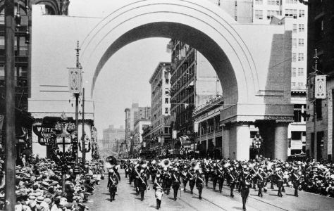 Playing Soldiers, a band marches south on Second Ave. though the welcoming arch at Marion Street for the Knights Templar conference here in 1925.