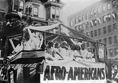 The Afro-American Float at the intersection of Second Avenue and Marion Street, with the Stetson Post Building (1883) behind it.