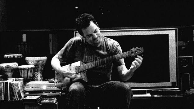 Paul Hepker, composer, tuning his Afri-can guitar. Playa del Rey, California, 2009