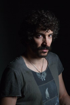 young man against black background, chain around neck, mustache and black curly hair