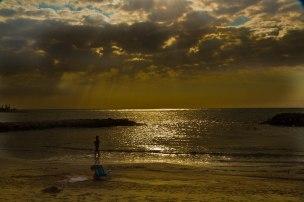 seascape man on beach sun shining through clouds