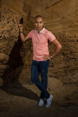 young man in jeans and pink top standing against rock wall