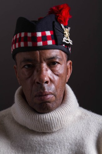 black man in white sweater and black hat with red and white squares and flower