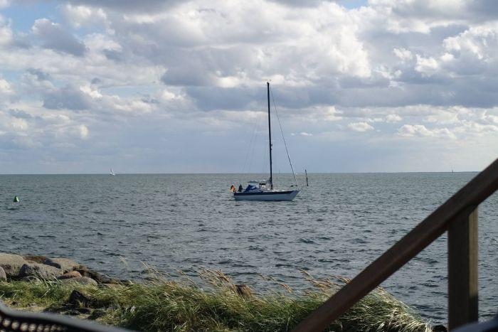 Auf dem Meer zieht ein Segelschiff vorbei