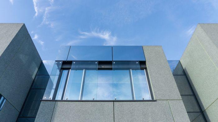 Die Fenster der Hochschule Dessau spiegeln den Himmel und die Wolken