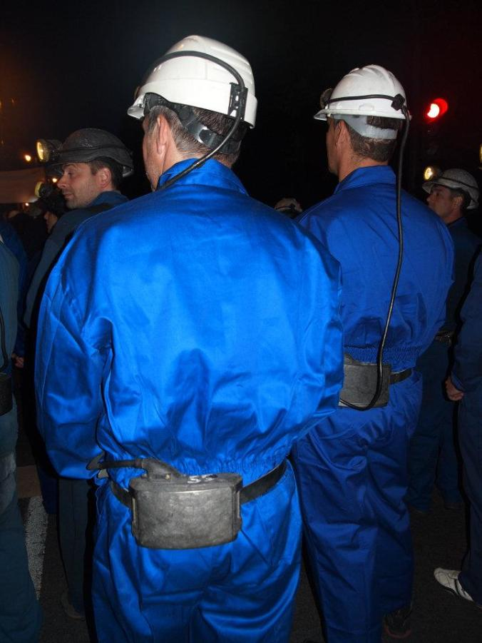 Dos personas vestidos de mineros con mono azul
