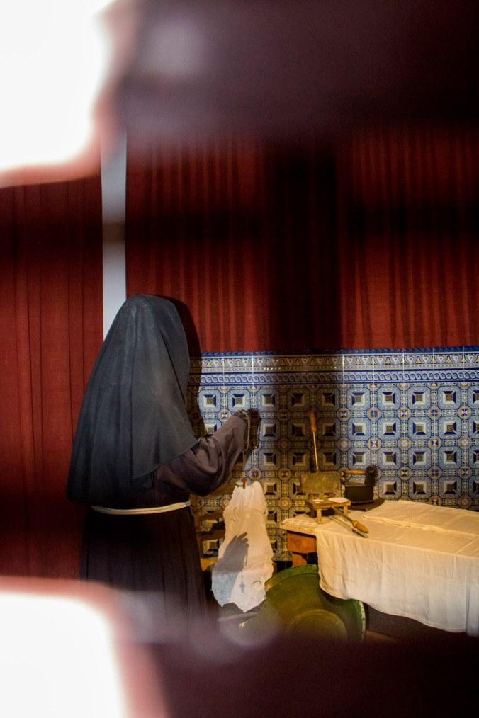 Monja rezando tras las verjas en Elche