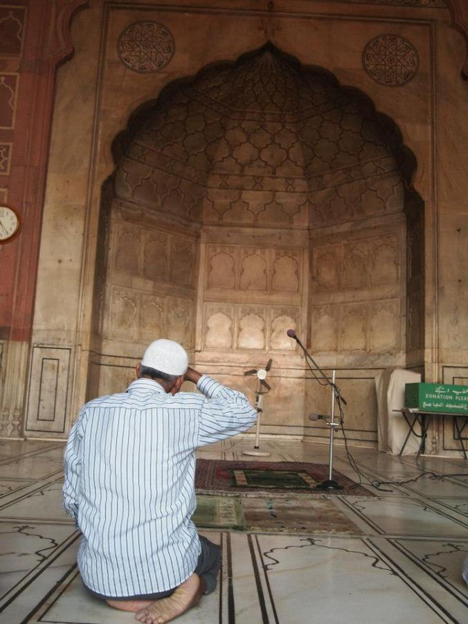 Hombre rezando en la mezquita de Masjid de Delhi